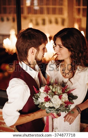 Stylish Wedding Couple, Groom and Bride with Flowers, Standing Together Embracing and Kissing in Loft Interior. Selective Focus. - stock photo