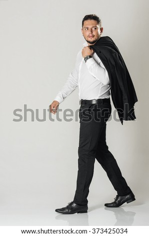 Stylish well dressed man walking with his jacket on the shoulder - stock photo