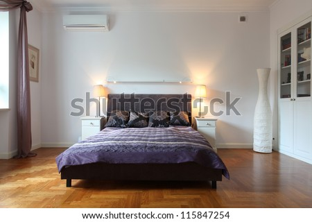Stylish white bedroom with a purple bed - stock photo