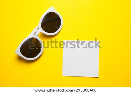 Stylish white sunglasses on yellow background with white paper frames - stock photo