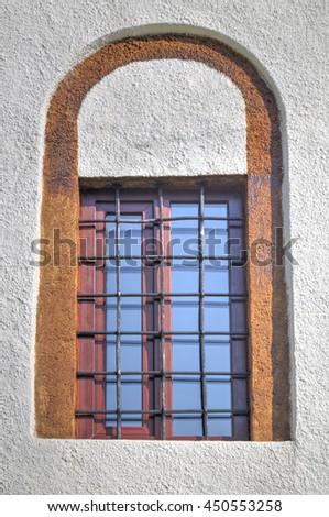 Stylish window with beautiful ornaments on white wall - stock photo