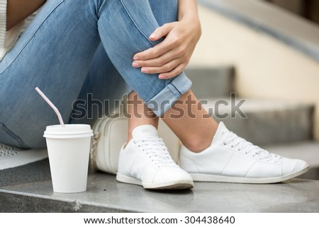 stylish woman drinking coffee to go in a city street - stock photo