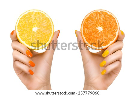 Stylish woman hands with orange and yellow colored nails holding slices of citrus fruits. Close up isolated on white background. Healthy clean eating diet concept - stock photo