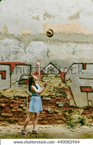 stylish woman hipster throwing her hat at old wall in european streets in sunny morning, space for text
