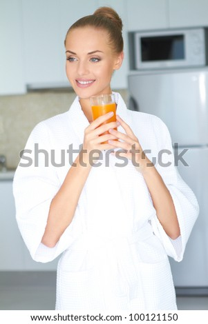 Stylish woman in a thick white towelling gown drinking a large glass of healthy orange juice