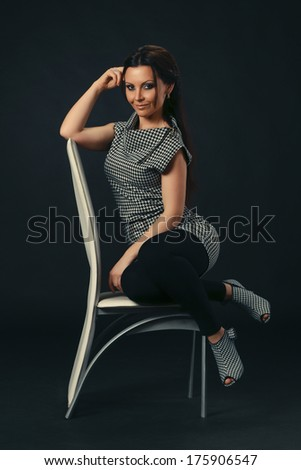 Stylish woman posing on a white chair in the studio