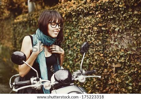 Stylish woman riding a motorbike - stock photo
