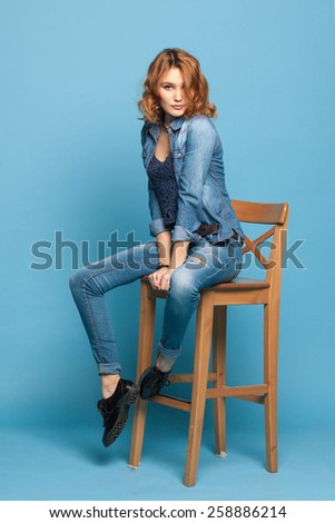 stylish woman sitting on a chair on a blue background - stock photo