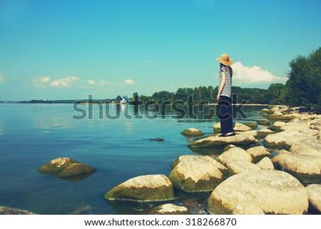 stylish woman standing along stone sea coast - stock photo