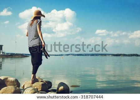 stylish woman walking along stone sea coast - stock photo