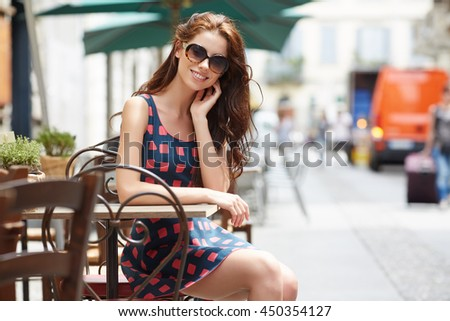 Stylish  woman, wearingsummer dresst,  posing at city cafe terrace, traveling clone, sunny day.