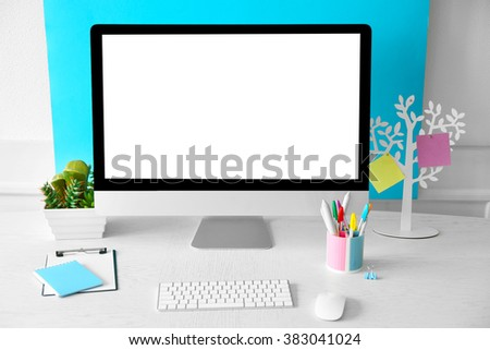 Stylish workplace with computer and interior decorations - stock photo