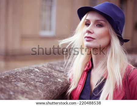 Stylish young blond woman waiting outdoors with her long hair blowing in the breeze leaning against a stone wall looking off to the left of the frame - stock photo