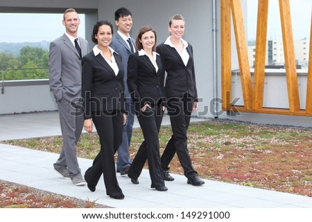 Stylish young business team of multiethnic men and women walking together along an outdoor cement pathway - stock photo