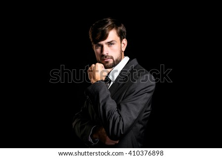 Stylish young businessman on black background. Businessman thoughtfully looking at camera