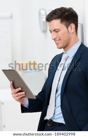 Stylish young businessman standing reading a handheld tablet computer smiling at the information on the screen - stock photo