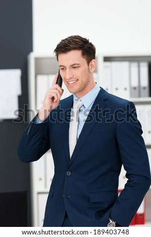 Stylish young businessman taking a call on a mobile phone standing listening to the conversation with a thoughtful expression and his hand in his pocket - stock photo