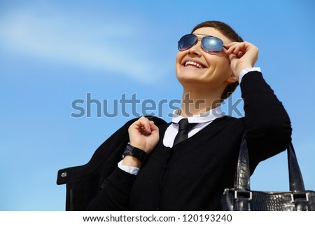 stylish young businesswoman in glasses with her handbag on background sky