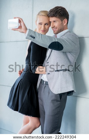 Stylish young couple in elegant evening wear taking a self-portrait on their mobile phone posing close together and smiling - stock photo