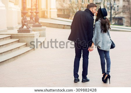 Stylish young couple walking on european autumn streets , have fun and hugging. Wearing trendy season outfit. Creamy  warm colors. - stock photo
