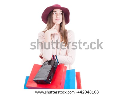 Stylish young female holding colorful shopping bags and thinking at something isolated on white with advertising area - stock photo
