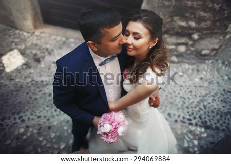Stylish young happy bride to the groom on the background ancient city in the mountains