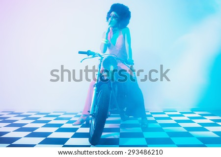 Stylish Young Lady on her Motorcycle Smoking a Cigarette Inside a Fuzzy Studio with Black and White Checkered Floor. - stock photo