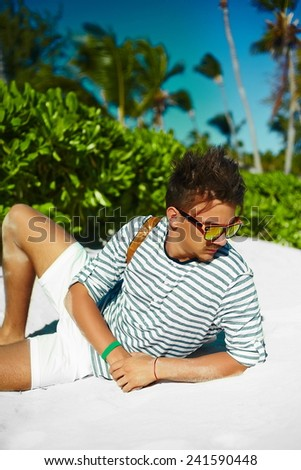 Stylish young male model man lying on beach sand  wearing hipster summer hat  enjoying summer travel holiday near ocean in sunglasses - stock photo