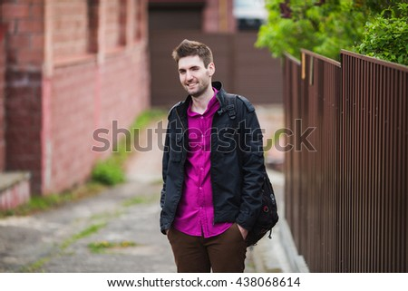Stylish young man in a purple shirt and a black jacket with a backpack on his shoulder, the guy smiling and winking - stock photo