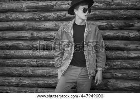 Stylish young man in casual free style clothes and hat over wooden background.