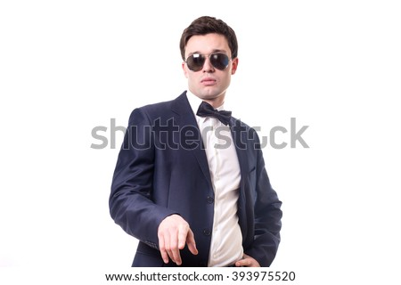 stylish young man in sunglasses, bow tie, dark suit and white shirt standing isolated on white background  - stock photo