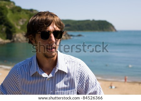 Stylish young man in sunglasses on the beach. - stock photo