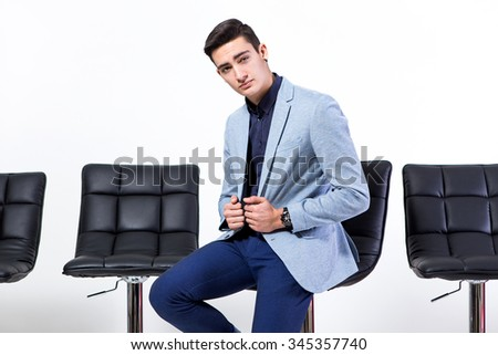 Stylish young man posing with bar stools on a white background