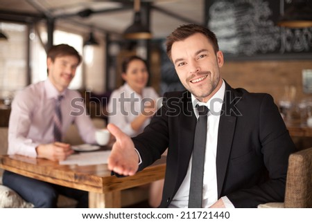 Stylish young man sitting in restaurant. closeup of smiling man giving hand and colleagues on background - stock photo