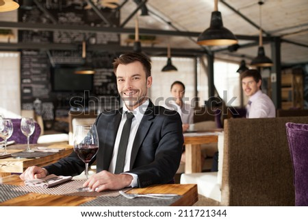 Stylish young man sitting in restaurant. Handsome man drinking glass of red wine in cafe - stock photo