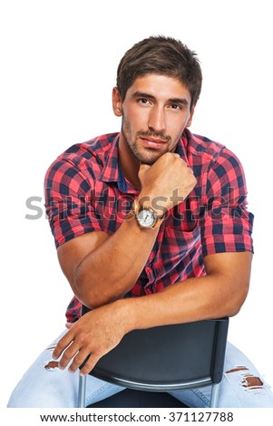 Stylish young man sitting on a chair in a red shirt and looking at the camera. Isolated on white background