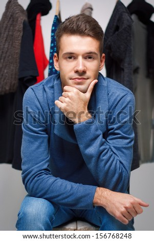 Stylish young man sitting on the background of the wardrobe - stock photo