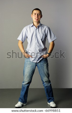 stylish young man standing with hands in pockets over gray background