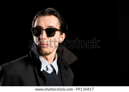 stylish young man wearing sunglasses looking away.