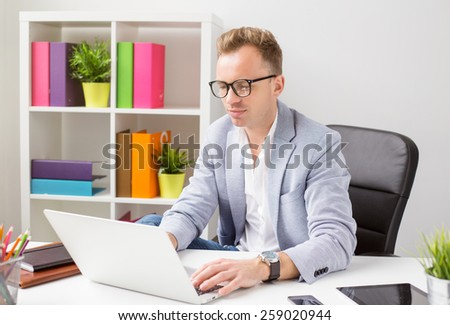 Stylish young man working with computer in office
