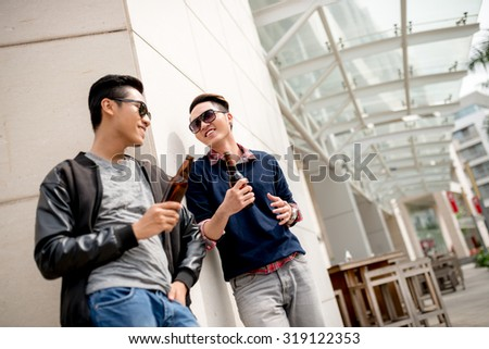 Stylish young people with beer bottles chatting in the street