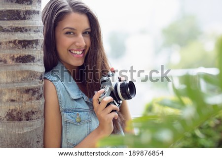 Stylish young photographer smiling at camera on a sunny day