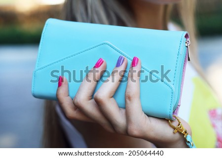 stylish young woman holding blue clutch in hand with pink manicure - stock photo
