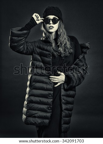 Stylish young woman in a down coat and knit cap.
