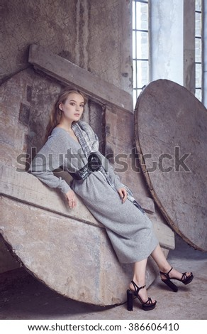 Stylish young woman in a long grey dress. - stock photo