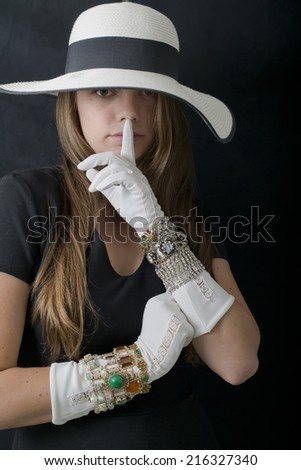 Stylish young woman in big floppy hat and long white gloves with finger to lips saying shhhhh I won't tell. - stock photo
