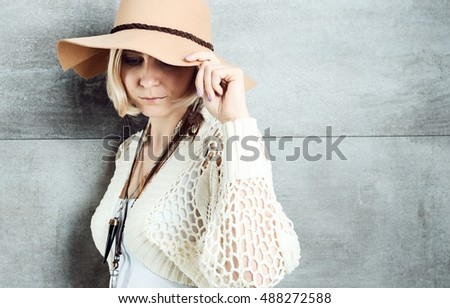 Stylish young woman in hat, looking down.