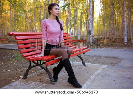 Stylish young woman on a red bench in a park in autumn