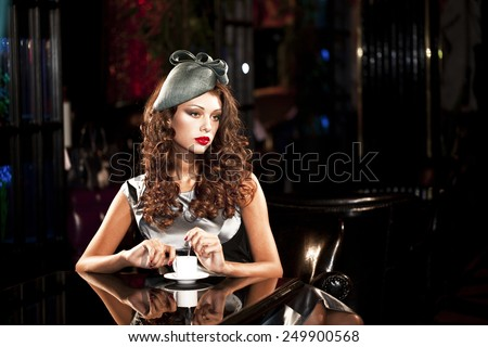 Stylish young woman sits at a table in a nightclub - stock photo