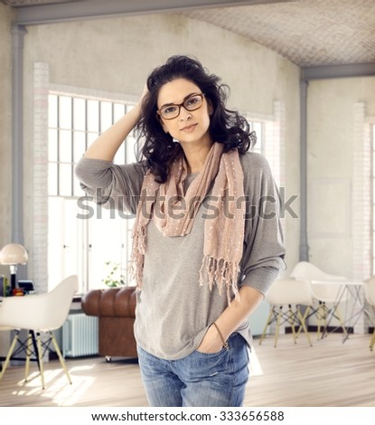 Stylish young woman standing in loft apartment, looking at camera, smiling hand in hair.
